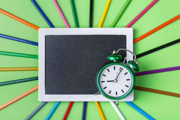 カラフルなレインボーペンシルとライムグリーンの背景に目覚まし時計