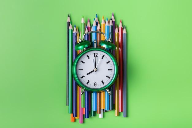 라임 녹색 배경에 화려한 무지개 연필과 알람 시계