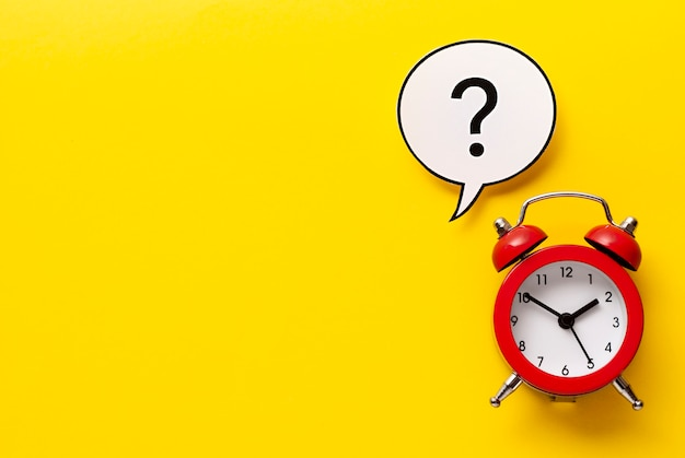 Colourful red alarm clock with question mark