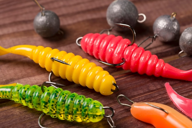 Colourful rubber fishing baits with plummets, close-up on wooden table