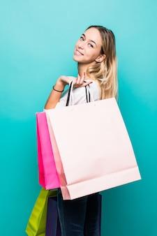 다채로운 쇼핑 분위기. 민트 벽에 화려한 쇼핑 가방과 함께 웃는 금발 여자의 전체 길이 초상화