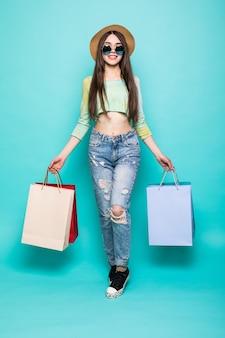Vibrazioni colorate per lo shopping. ritratti integrali di donna bruna sorridente in cappello e vestiti luminosi con i sacchetti della spesa in esecuzione