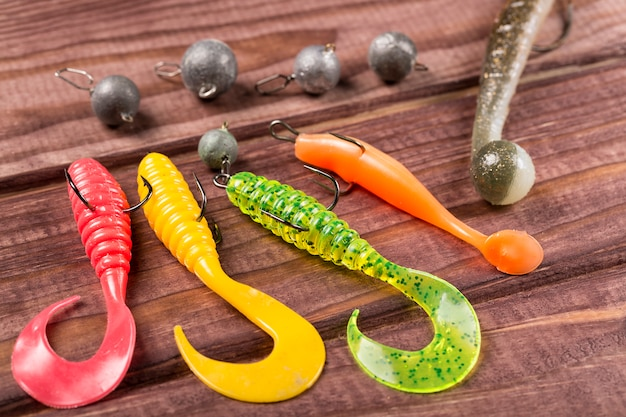 Colourful silicone fishing baits with plummets, close-up on wooden table