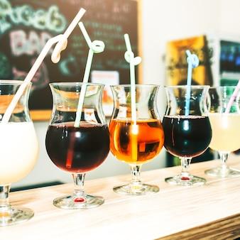 빨대와 안경에 다채로운 여름 칵테일입니다. 바 카운터에 서 있는 음료. 와인, 피나콜라다, 사과 주스. 여름 날씨에 신선하고 차갑습니다.