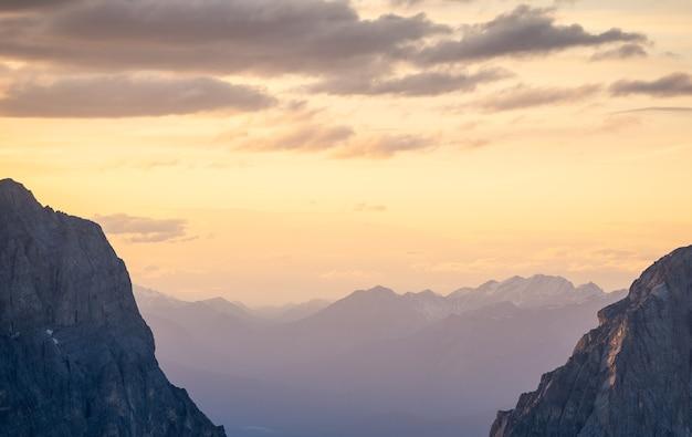 カナダのrockiesrimwallsummitcanadaの山脈の上のカラフルな夕焼け空