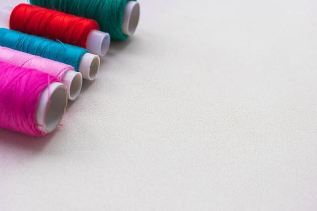 白で隔離されるカラフルな糸スプール