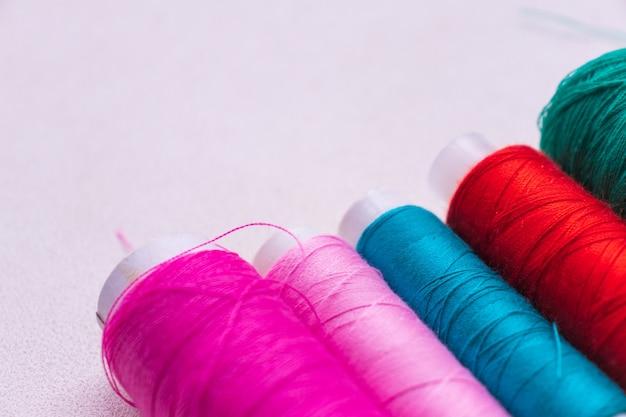 白で隔離されるカラフルな糸のスプール