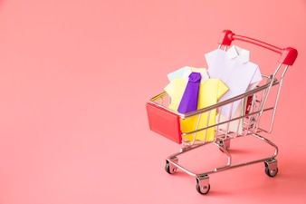 Colourful toy paper shirts in shopping trolley