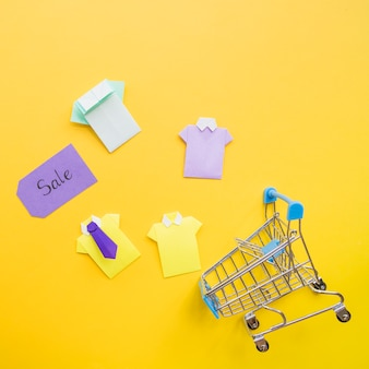Colourful toy paper shirts near shopping trolley and sale tag