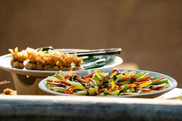 블라인드 모양으로 다채로운 야채 슬라이드를 함께 묶고 오순절 접시에 놓습니다.