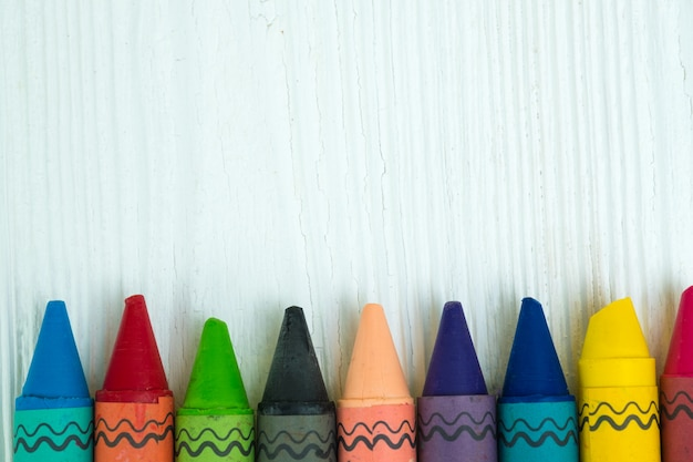Colourful wax crayons pencils on white wood table