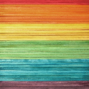 Colourful wooden wall texture in bright rainbow swatch pattern.