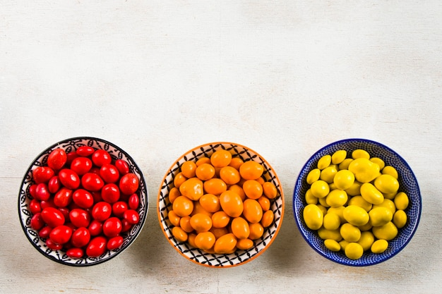 Colourfull candies in bowls on white, top view Premium Photo