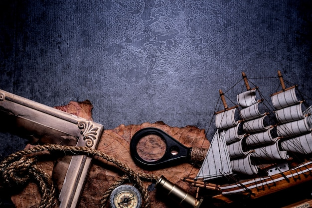 콜럼버스의 날. 월드맵과 발견 장비를 갖춘 해적과 보물. 어두운 배경에 공간을 복사합니다.