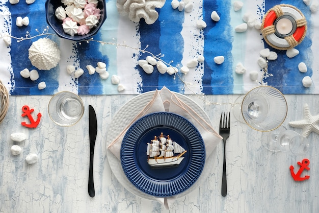 Columbus day table setting with nautical sea decorations on blue and white stripy runner,
