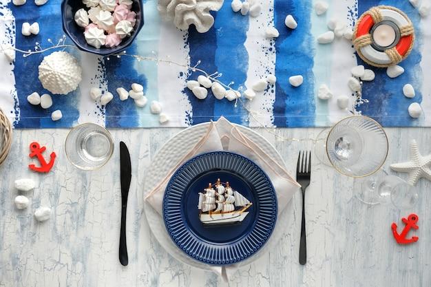 Сервировка стола columbus day с морскими украшениями на сине-белой полосатой дорожке,