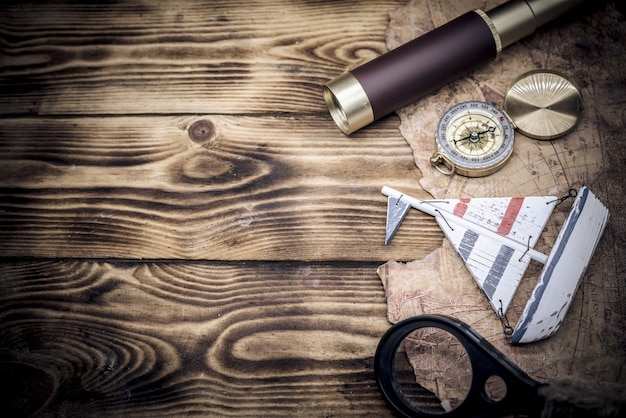 Columbus day. vintage worldmap and discovery equipment. copy space on dark wood background.