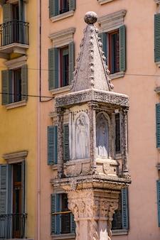 イタリア、ヴェローナのエルベ広場の柱。この14世紀のコラムには、聖母マリアと聖人ゼノ、クリストファー、ピーターのレリーフがあります。