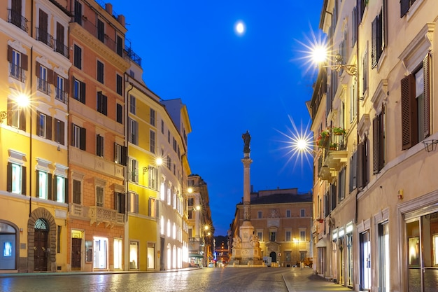 The column of the immaculate conception depicting the blessed virgin mary, on piazza mignanelli during morning blue hour, rome, italy.