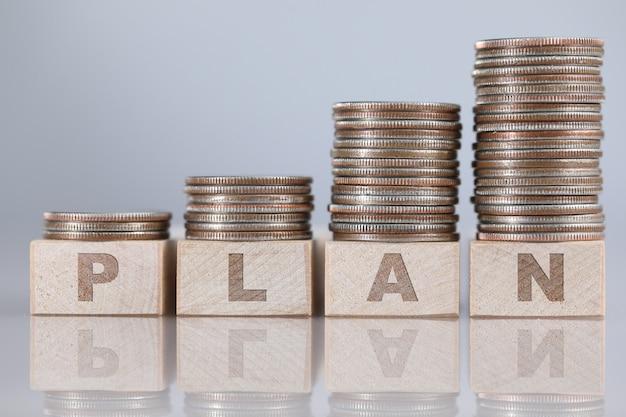 計画利益のクローズアップの指数関数的な上昇チャートとして木製キューブに立っている銀の四分の一の列