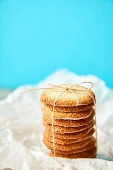 ターコイズの背景にギフト用のロープで結ばれたおいしいクッキーの列