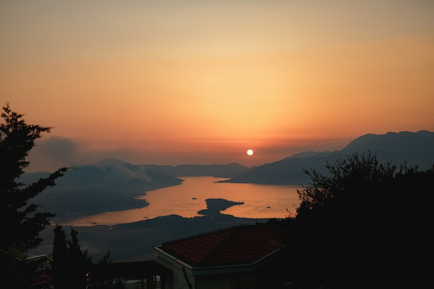 A column of smoke on the lustica peninsula in montenegro wildfires rage at sunset