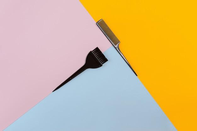 색상 분홍색, 노란색, 파란색 종이 배경에 빗과 브러시. 평면도. 공간을 복사합니다. 정물. 모형. 플랫 레이