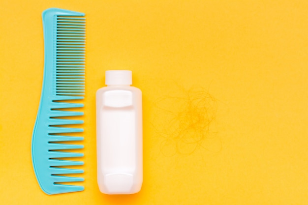 Comb, bottle with balm and a hank of fallen hair on a yellow background
