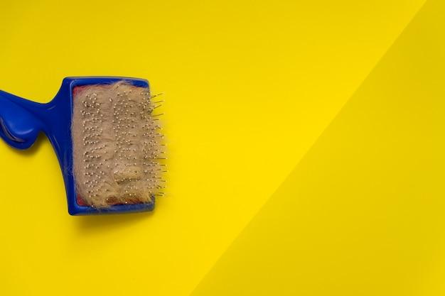 黄色のテーブルに動物の毛とグレーのウールのくし。動物のヘアブラシ。