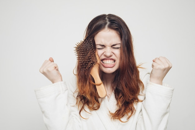 Comb stuck in the hair of an emotional woman on a light background