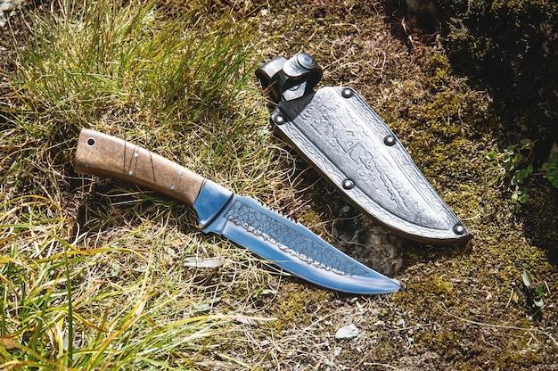 森の草の上に横たわる鞘との戦闘ナイフ。概念の野生での生存