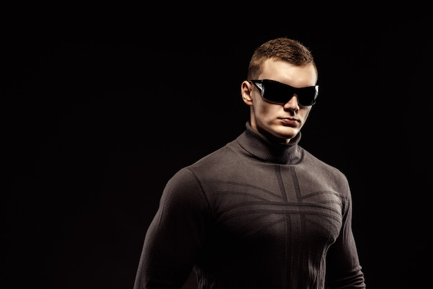 Combat muscled action hero man wearing brown sweater and sunglasses