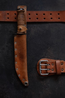 Combat soldier stainless steel fighting knife with leather handle, scabbard and leather belt in  wooden vintage frame.