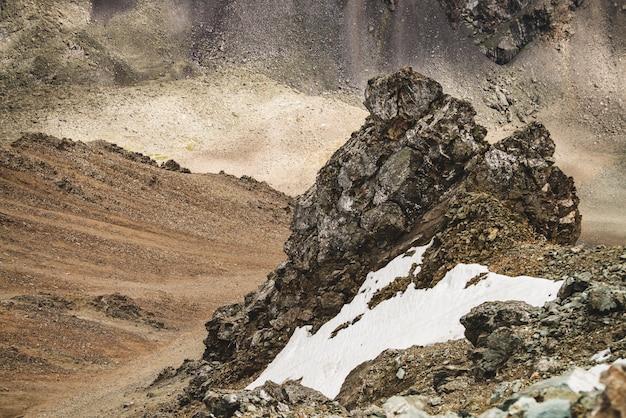 Атмосферный альпийский пейзаж с елью или снег возле каменистого утеса крупным планом на горной стене на combe скалистом холме. снежная скалистая гора потока валуна. величественные пейзажи на большой высоте.
