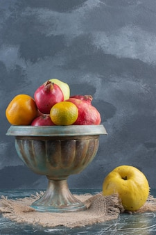 Combination of autumn fruits in platters on blue surface.