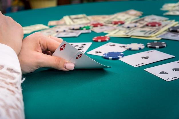 포커 테이블에 여성 손에 두 개의 에이스의 조합