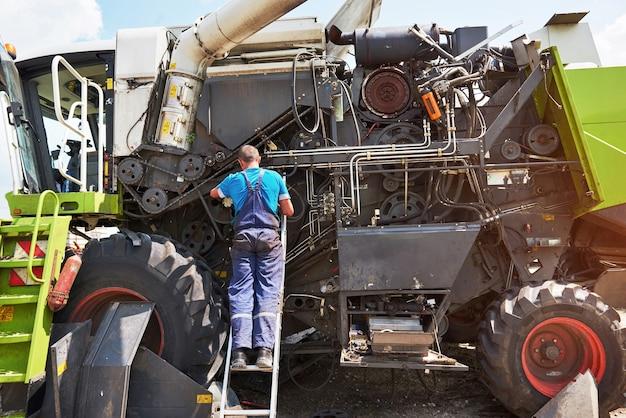 Combine machine service, mechanic repairing motor outdoors.