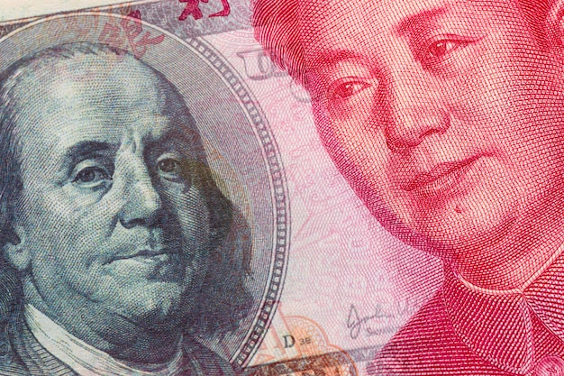Combined image of the 100 yuan chinese currency and the 100 american dollar banknotes.