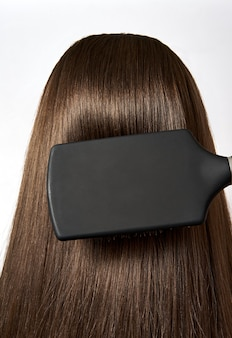 Combing healthy long straight brown female hair close up