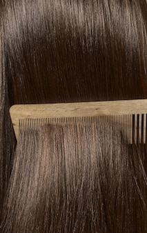 Combing healthy long straight female hair. close up
