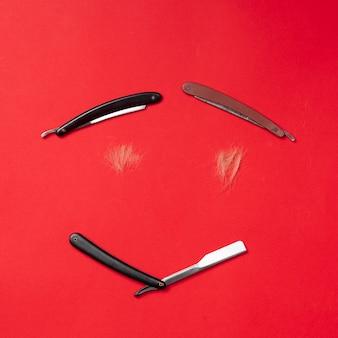 Расчески и парикмахерские инструменты на красном вид сверху