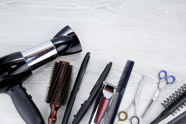 木製の背景に美容院のデスクトップではさみと理髪ツールをとかします