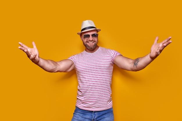 가까이 오세요. 트렌디한 벗겨진 옷을 입은 긍정적인 수염 난 남자의 스튜디오 샷을 안아주세요...