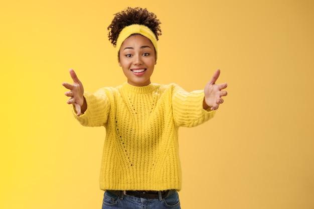 Avvicinati, lascia che ti abbracci. toccato adorabile felice giovane afro-americana bella donna estende le braccia vuole tenere affascinanti braccia del bambino carino chiedendo coccole abbraccio amichevole, in posa sfondo giallo.