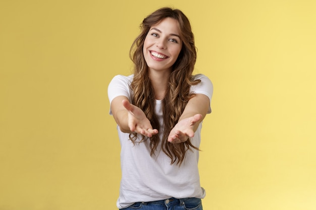 Come closer take my hand. cheerful lovely charismatic tender woman extend arms forward camera wanna hold receive charming gift tilt head smiling pleased grateful stand yellow background. copy space