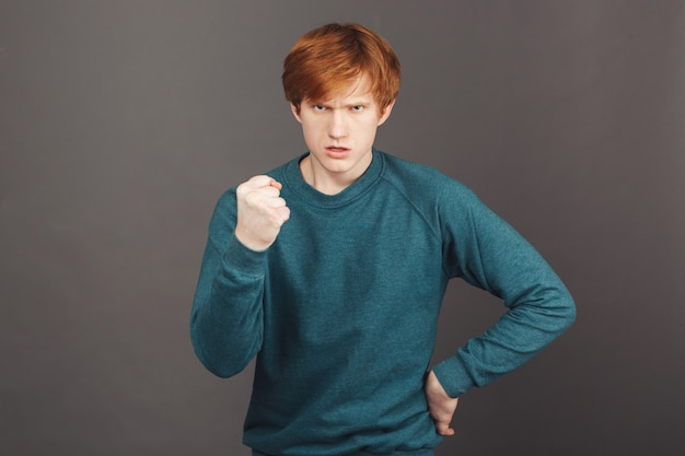 Come here, boy. young mean ginger young european student guy in green sweater showing fist