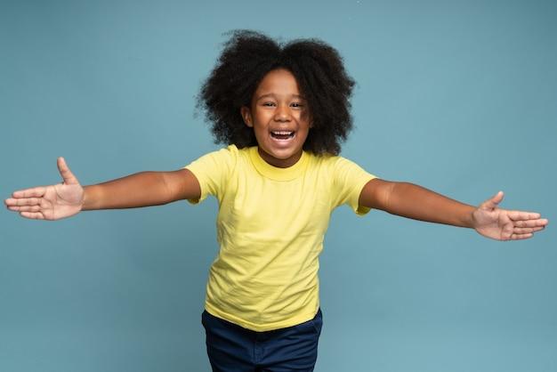 이리와 무료 포옹 노란색 티셔츠에 곱슬 머리를 가진 사랑스러운 착한 어린 소녀의 초상화