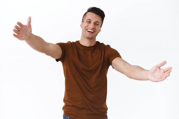 여기로 오세요, 사랑하는 친구. 포옹을 위해 손을 뻗고 있는 친절하고 웃는 성인 남성의 초상화, 손님을 맞이하는 사람