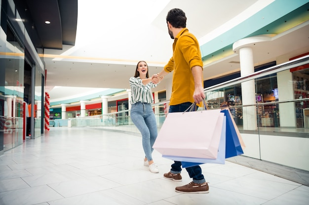 Come on honey. full length photo of cheerful pretty lady lead hands handsome guy to next store wanna buy one more shirt dress shoes many bags shopping center wear casual outfit indoors
