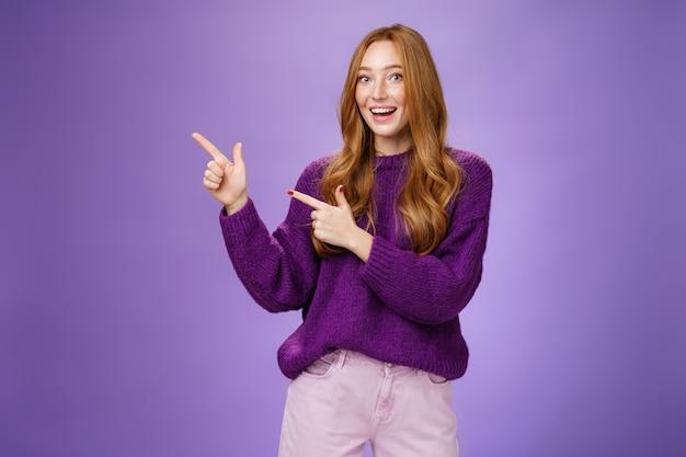 보라색 스웨터를 입은 친근하고 쾌활한 예쁜 생강 소녀의 초상화로 우리를 방문하십시오 ...